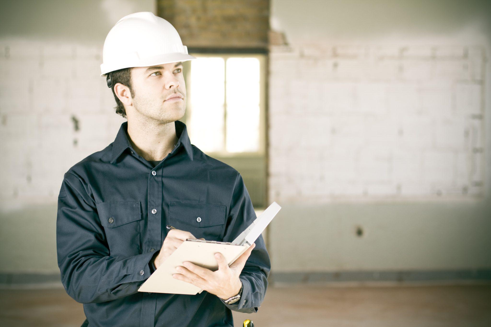 Un travailleur inspecte un bâtiment en prenant des notes