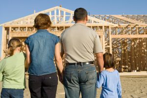 Une famille satisfaite admire la charpente de leur futur maison en construction